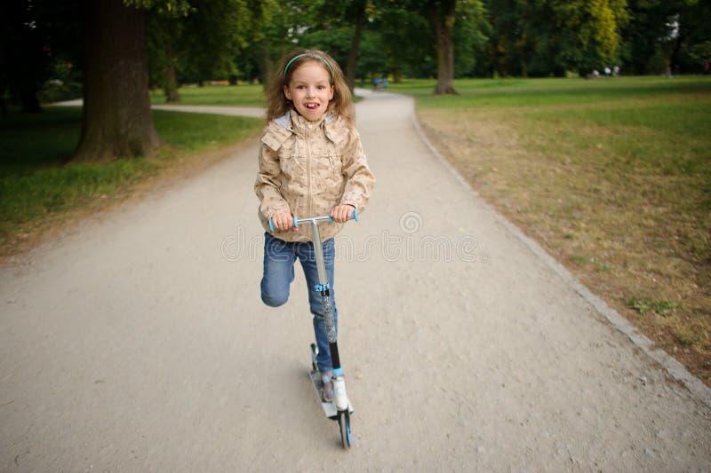La muchacha de 7-8 años acomete en la vespa en una trayectoria en parque imagenes de archivo