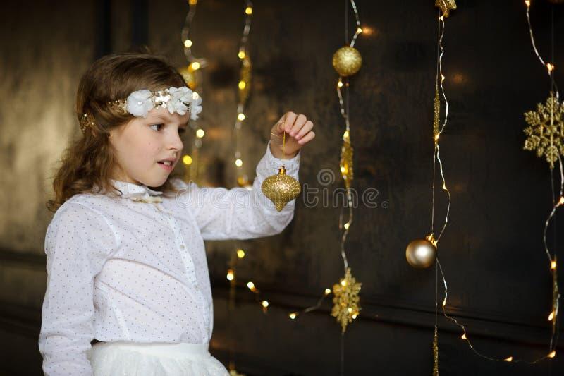 La muchacha de 8-9 años con placer admira decoraciones del árbol de navidad del oro fotos de archivo