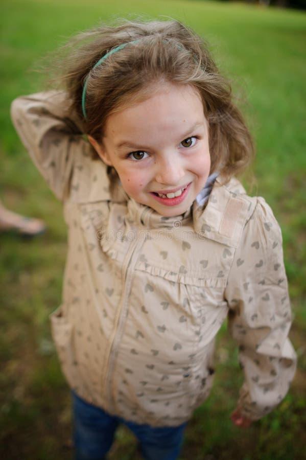La muchacha de 7-8 años con una sonrisa mira la cámara fotografía de archivo