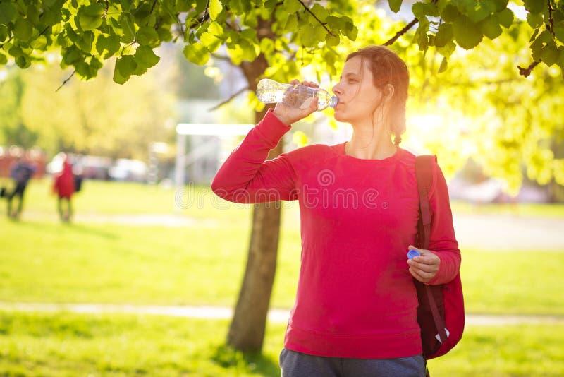 La muchacha de la aptitud en parque del verano bebe el agua de la botella Mujer joven en al aire libre soleado fotografía de archivo
