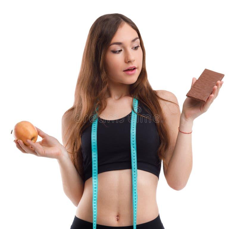 La muchacha de la aptitud en una mano que sostenía una manzana en otro chocolate en blanco aisló el fondo imagenes de archivo