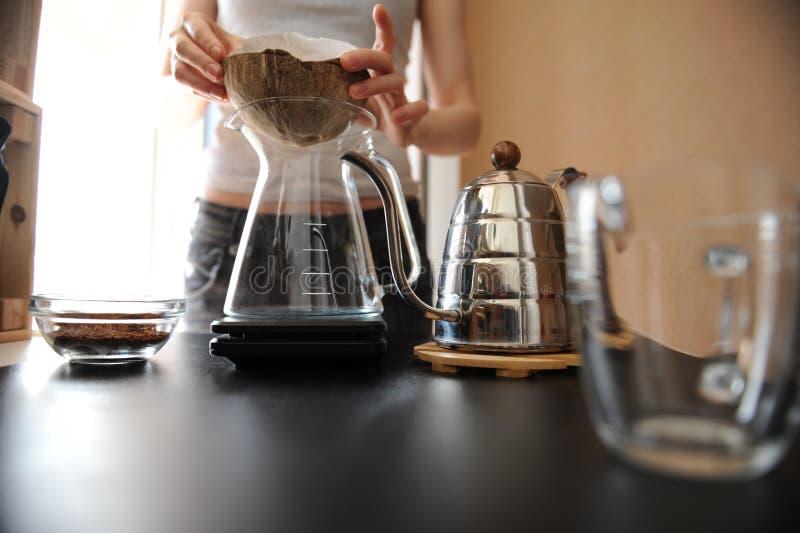 La muchacha de Barista prepara el café en una cáscara inusual del coco del purover de la cáscara del coco imágenes de archivo libres de regalías
