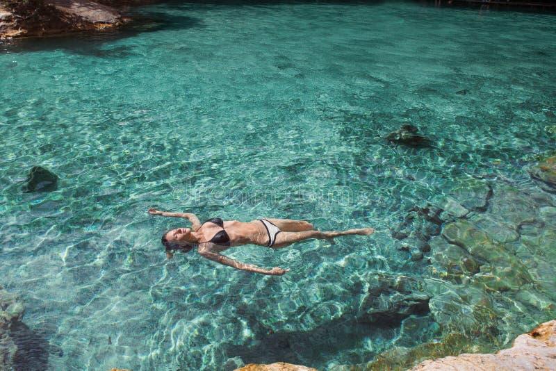 La muchacha de Bautiful se relaja en laguna azul fotografía de archivo