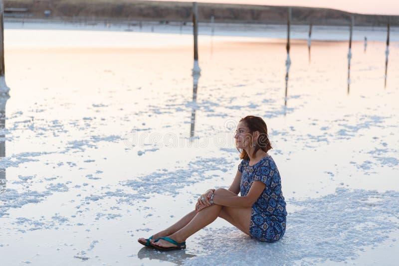 La muchacha de la calma que goza del sol, se sienta en la tierra cubierta con la sal cerca del lago fotos de archivo