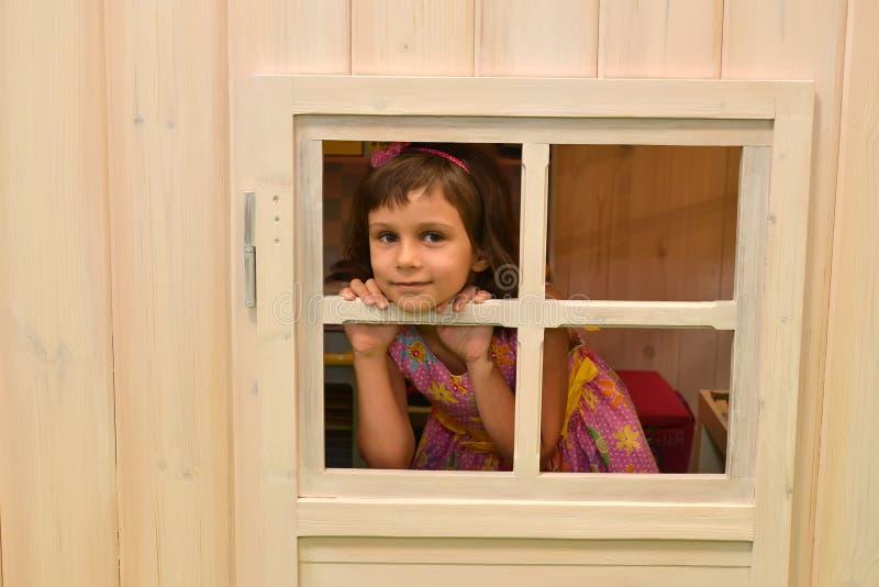 La muchacha de cinco años mira hacia fuera en una ventana de la casa de campo kindergarten imagen de archivo libre de regalías