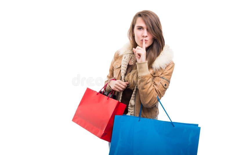 La muchacha de compras elegante indica gesto del silencio fotos de archivo