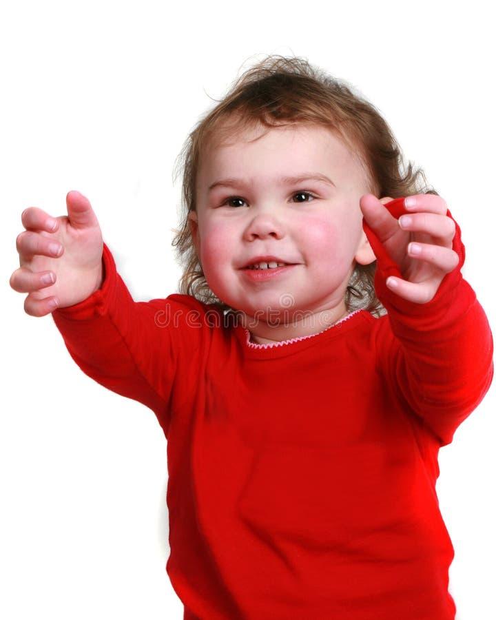 La muchacha de dos años que la alcanza reparte foto de archivo libre de regalías