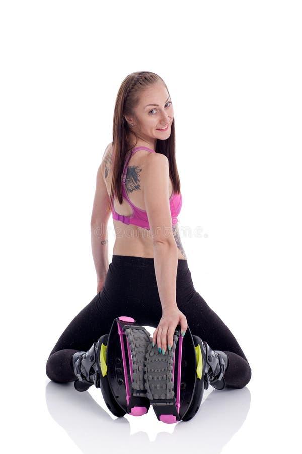 La muchacha de la aptitud que ejercita con kangoo salta los zapatos foto de archivo