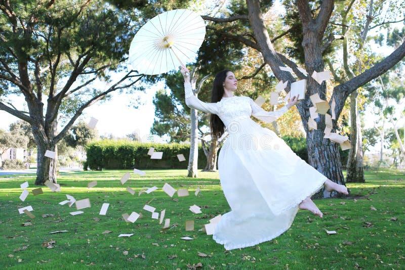 La muchacha de la levitación al aire libre con el libro pagina el vuelo foto de archivo libre de regalías
