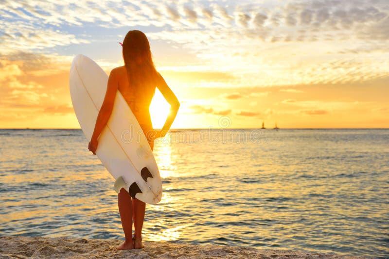La muchacha de la persona que practica surf que practica surf que mira el océano vara puesta del sol imagenes de archivo