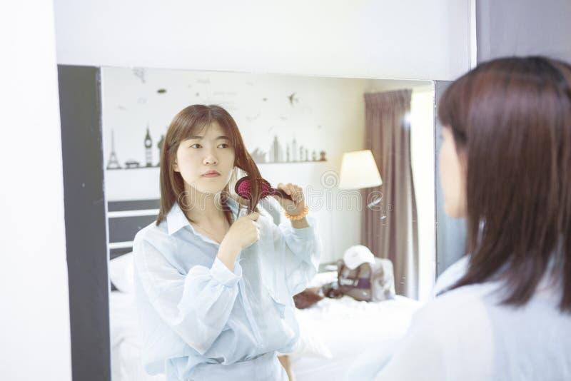 La muchacha de los asiáticos está cepillando su pelo en espejo delantero en la mañana foto de archivo