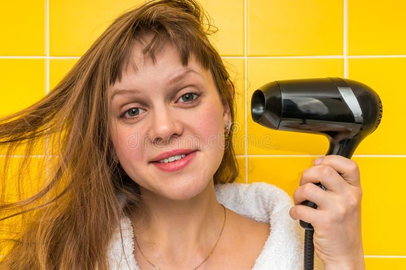 La muchacha de la moda con el secador de pelo negro se seca el pelo imagenes de archivo