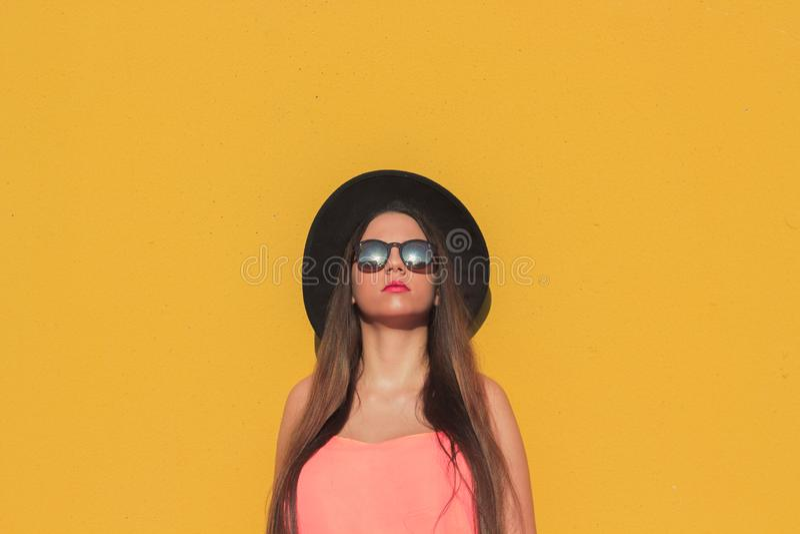La muchacha de moda con las gafas de sol y el sombrero negro con una pared amarilla como fondo fotos de archivo