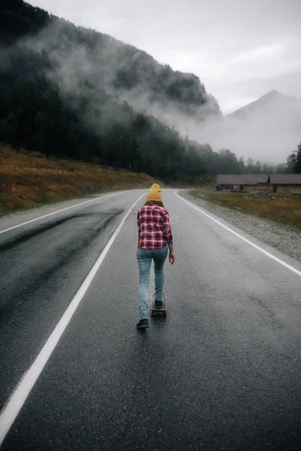 La muchacha de moda del inconformista monta un monopatín en el camino en las montañas alrededor de la montaña y de la hermosa vis fotografía de archivo