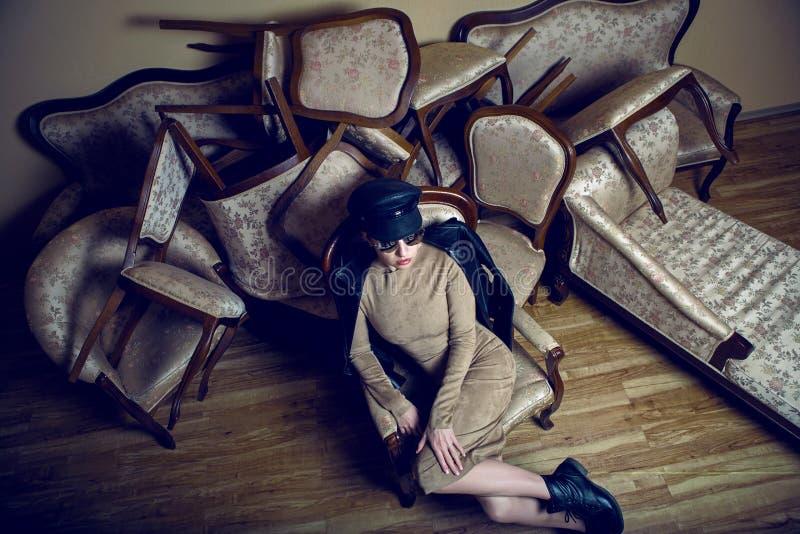 La muchacha de moda en una chaqueta de cuero y un casquillo miente en el sofá imagen de archivo