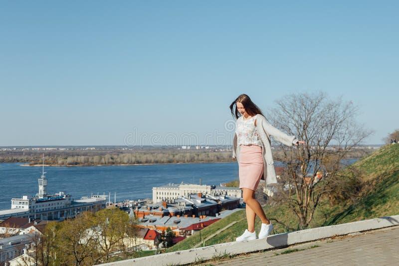 La muchacha de moda está en el parapeto, equilibrando fotografía de archivo libre de regalías