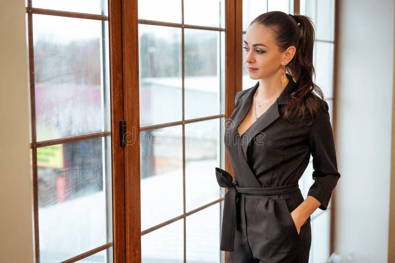 La muchacha de moda se coloca en la ventana y mira la ropa elegante imagen de archivo