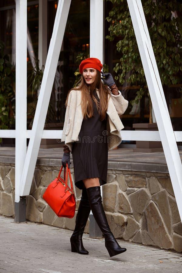 La muchacha de moda vestida en el vestido gris elegante, la capa de zalea corta, los guantes y la boina roja sosteniendo un bolso imagen de archivo libre de regalías