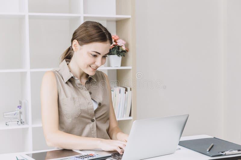 La muchacha de oficina de la mujer de negocios goza el trabajar en el escritorio con el ordenador port?til fotos de archivo