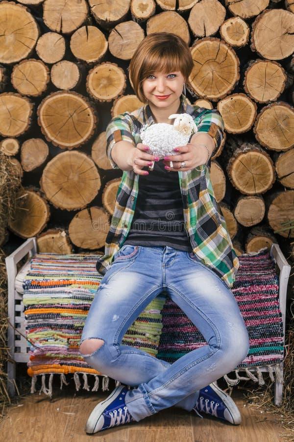 La muchacha de pelo corto joven linda se sienta y sosteniendo el cordero del juguete en un banco rústico Fondo de madera Cultivo  fotografía de archivo libre de regalías