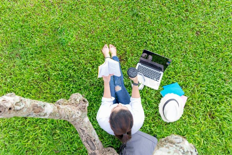 La muchacha de la persona de la forma de vida goza el leer de un libro y de un ordenador portátil del juego en el campo de hierba imagen de archivo libre de regalías