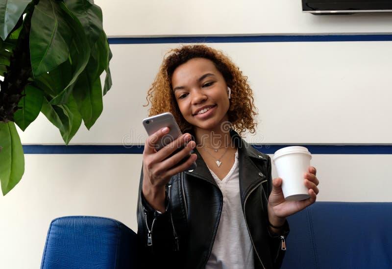 La muchacha de piel morena con un vidrio de café es sonriente y de mirada de un teléfono móvil Sala de espera en la estaci?n del  fotos de archivo libres de regalías