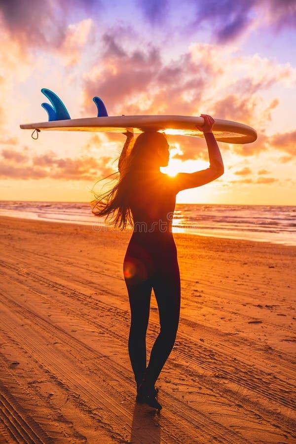 La muchacha de la resaca con el pelo largo va a practicar surf Mujer joven con la tabla hawaiana en una playa en la puesta del so fotografía de archivo