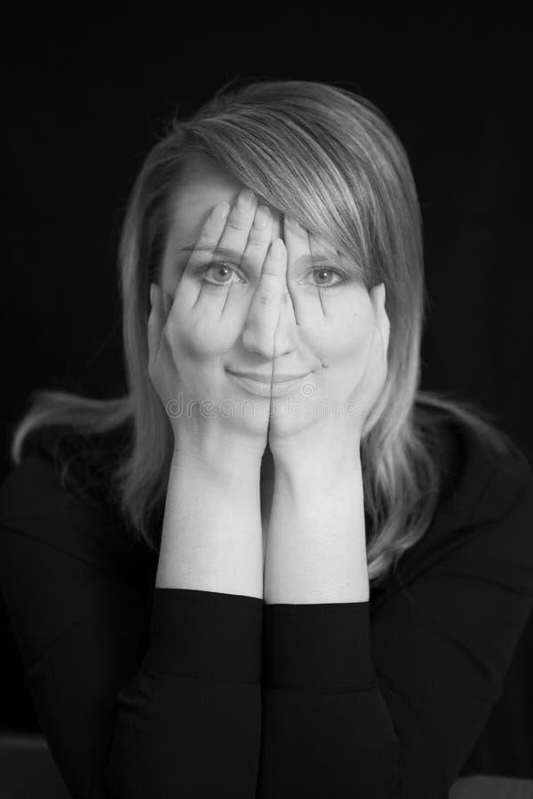 La muchacha de risa bonita cubrió la cara con sus manos y mirar a escondidas a través de sus fingeres imagen de archivo libre de regalías