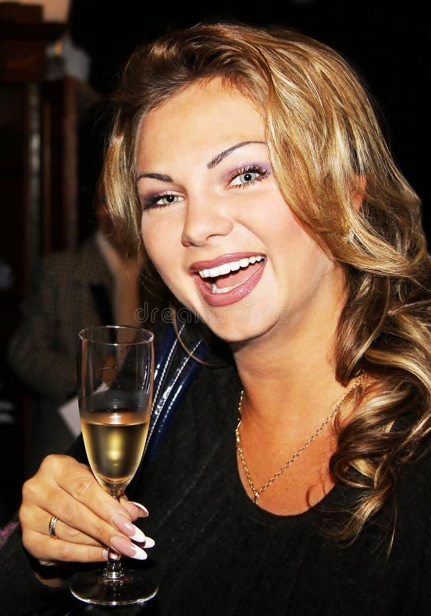 La muchacha de risa con un vidrio del champán foto de archivo libre de regalías
