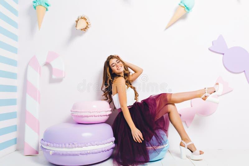La muchacha de risa Inspired en el vestido enorme de moda que se enfriaba en silla azul de los macarrones con los ojos se cerró E imagenes de archivo