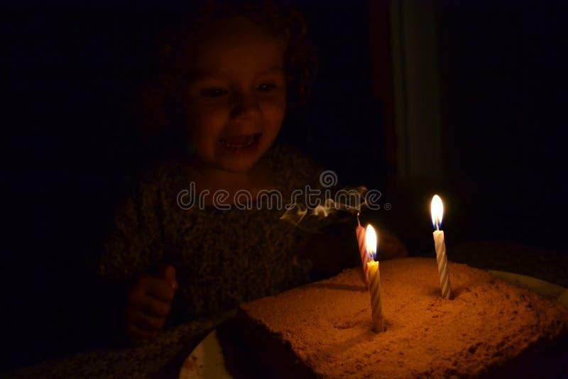 La muchacha de risa puso hacia fuera una vela ardiente foto de archivo libre de regalías