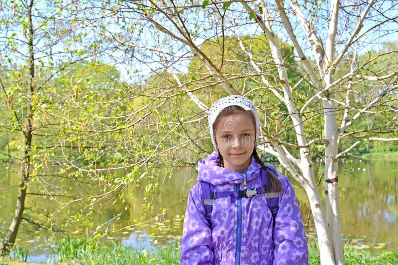 La muchacha de siete años contra la perspectiva de los árboles florecientes en el parque Primavera imagen de archivo