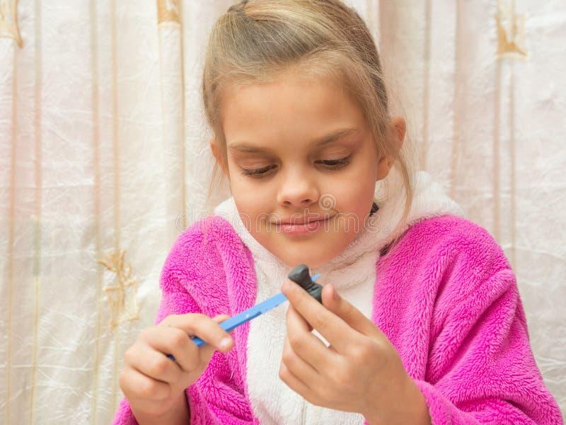La muchacha de siete años en pila hace artes del dibujo de la arcilla imagenes de archivo