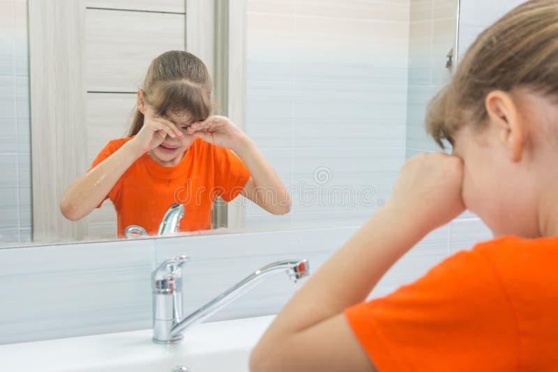 La muchacha de siete años la frota los ojos que intentan despertar foto de archivo libre de regalías