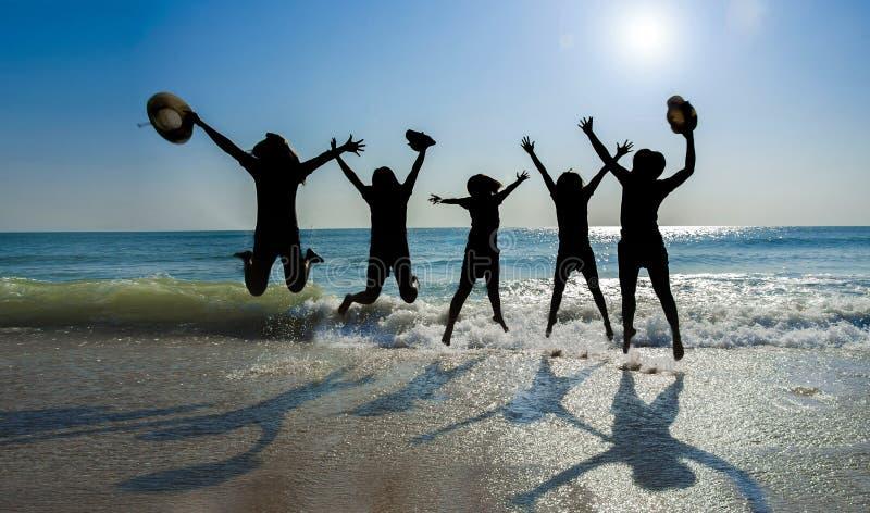 La muchacha de Sillhuettes salta en la playa imagen de archivo