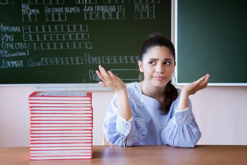 La muchacha de Supdrised en vidrios se sienta contra la pizarra en sala de clase imagen de archivo