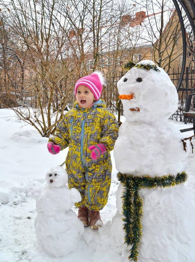 La muchacha de tres años alegre cuesta cerca de un muñeco de nieve foto de archivo libre de regalías