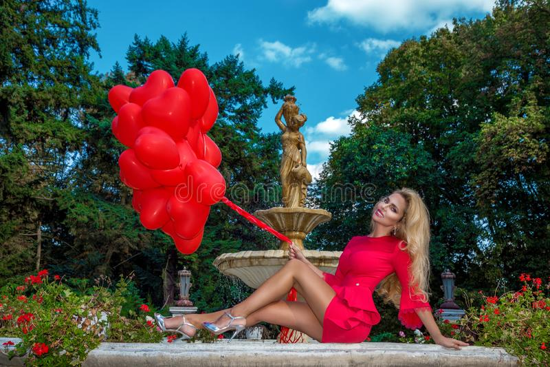 La muchacha de Valentine Beautiful con los globos rojos ríe, en el parque Mujer joven feliz hermosa Fiesta de cumpleaños foto de archivo libre de regalías