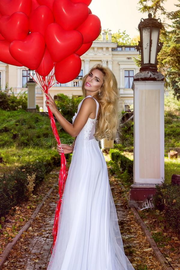 La muchacha de Valentine Beautiful con los globos rojos ríe, en el parque Mujer joven feliz hermosa Fiesta y novia de cumpleaños  foto de archivo