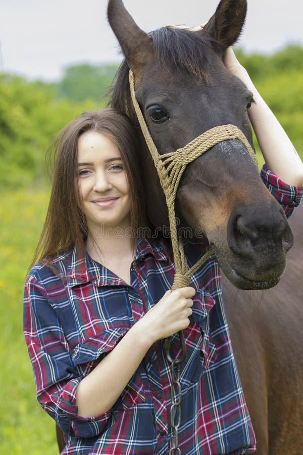 La muchacha del adolescente abraza el caballo imagenes de archivo