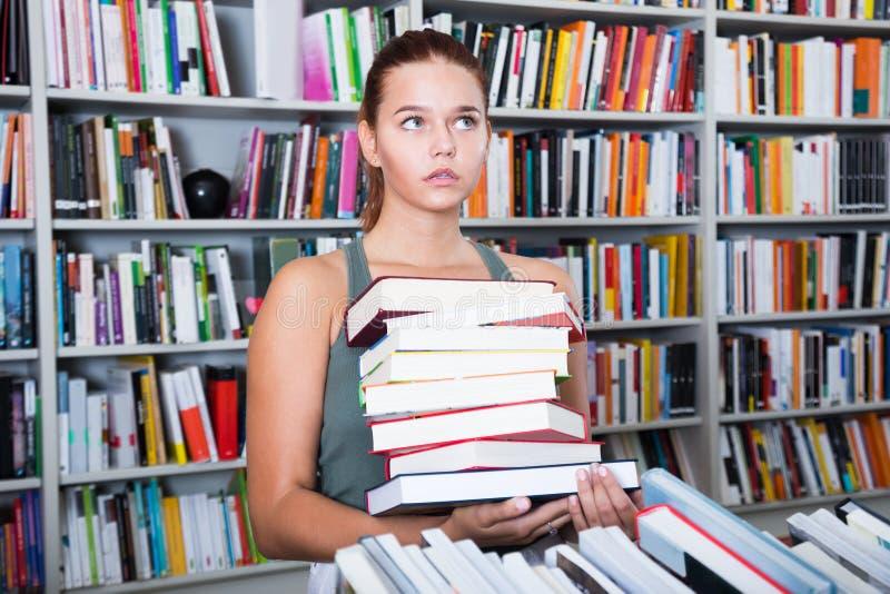 La muchacha del adolescente busca el libro derecho en biblioteca foto de archivo
