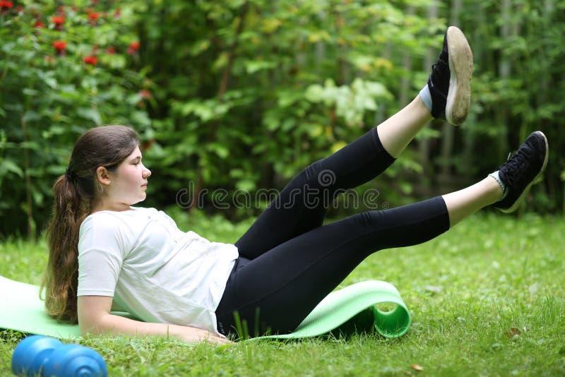 La muchacha del adolescente pone agotado en el trapo del gimnasio con pesa de gimnasia después de ejercicios del tren foto de archivo
