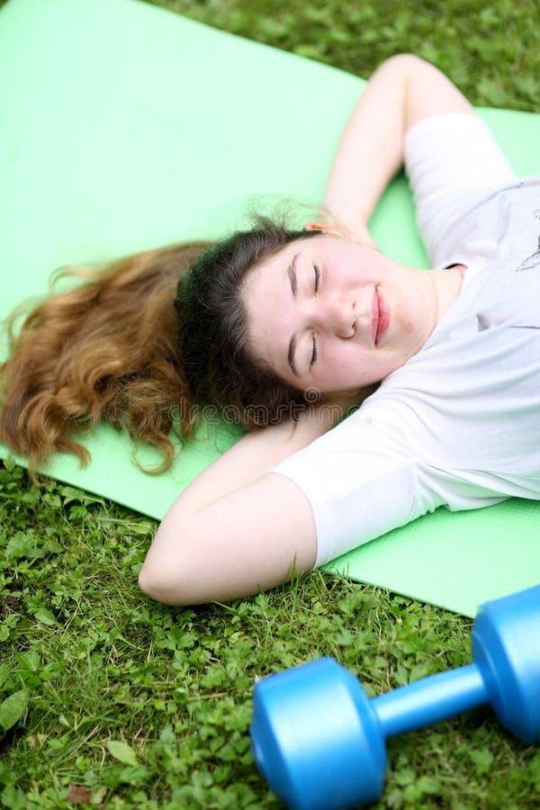 La muchacha del adolescente pone agotado en el trapo del gimnasio con pesa de gimnasia después de ejercicios del tren foto de archivo libre de regalías