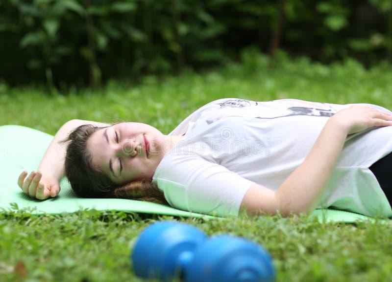La muchacha del adolescente pone agotado en el trapo del gimnasio con pesa de gimnasia después de ejercicios del tren imagen de archivo