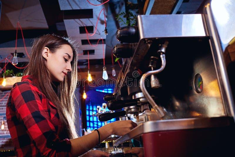 La muchacha del camarero está haciendo el café en una barra fotografía de archivo libre de regalías