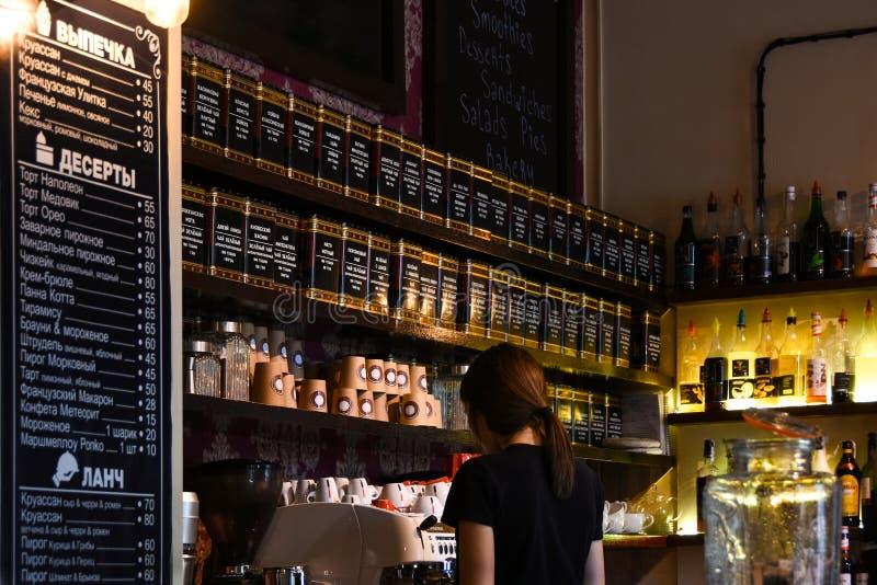 La muchacha del camarero está preparando el té para el visitante del café El interior de la barra fotografía de archivo libre de regalías
