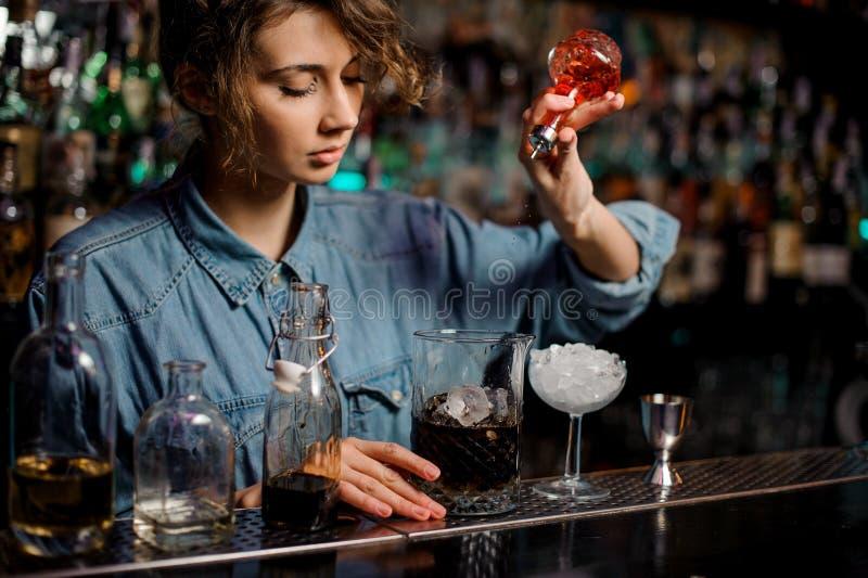 La muchacha del camarero que vierte a la taza de medición con hielo cubica un amargo rojo de la botella de cristal imagen de archivo libre de regalías