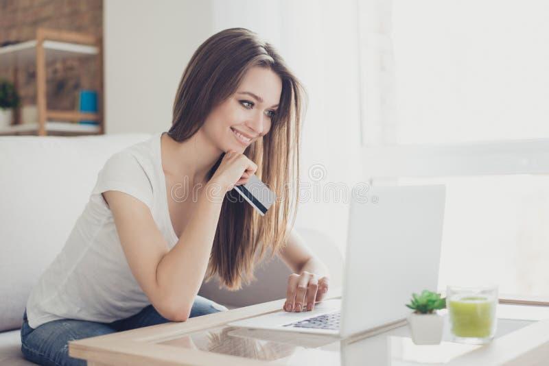La muchacha del comprador está comprando en línea con un ordenador portátil y un sitt de la tarjeta de crédito fotos de archivo libres de regalías