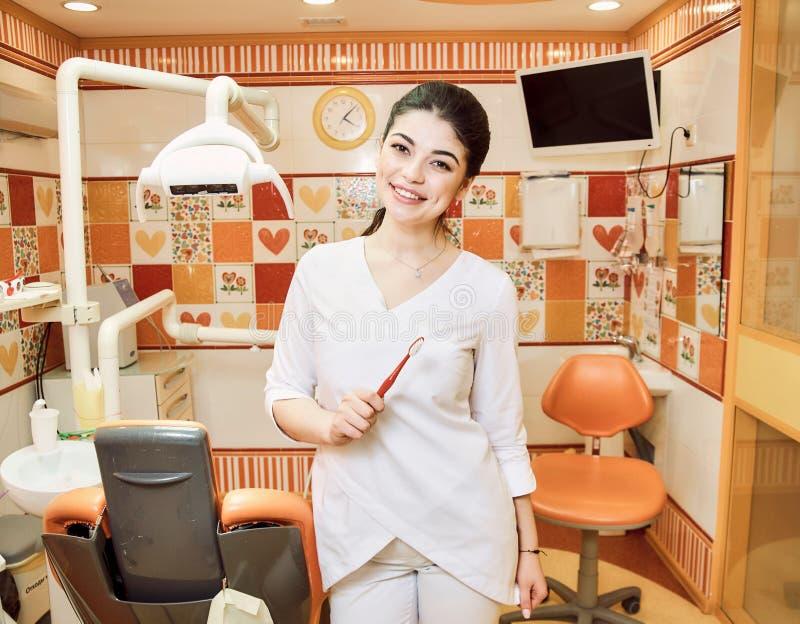 La muchacha del dentista de los niños en la oficina del dentista guarda su cepillo de dientes fotos de archivo