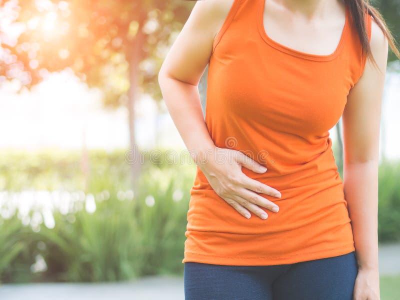 La muchacha del deporte tiene dolor de estómago después de activar al ou del trabajo imagenes de archivo